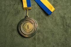 Gold medal for first place with yellow and blue ribbon stock images