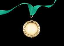 Gold medal with green ribbon Stock Photos