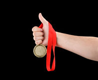 Gold medal in hand isolated. On black Royalty Free Stock Photos