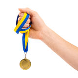 Gold medal in hand on white background. Gold medal in hand isolated on white background Royalty Free Stock Photography