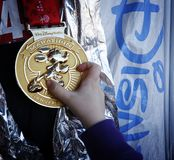 Gold Medal. January 12, 2014, Walt Disney World, Florida, Marathon: Child holding Walt Disney Marathon gold medal with running Mickey Mouse Royalty Free Stock Image