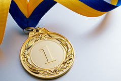Gold medal on a light background. Gold medal in the foreground on yellow blue ribbon Royalty Free Stock Photography