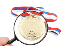 Gold medal and magnifying glass isolated Stock Photography