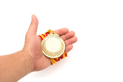 Gold medal on males hand on white background. Gold medal on males hand on a white background Royalty Free Stock Photos