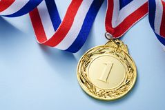 Gold medal 1 place with a ribbon. On a light blue background, the concept of victory or success stock photo