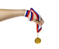 Gold Medal on a Ribbon in a child's hand Royalty Free Stock Image