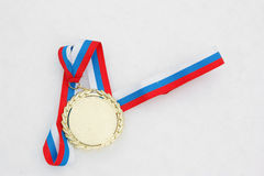 Gold medal with ribbon in snow Stock Photos