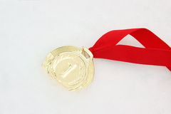 Gold medal with ribbon in snow Stock Images