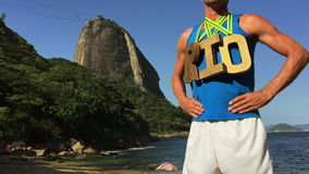Gold Medal RIO Athlete Standing at Sugarloaf Mountain. RIO 2016 first place athlete wearing gold medals standing outdoors turning in the sun in front of stock footage