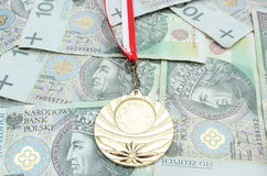 Gold medal and roll of tied banknotes on money background Stock Image