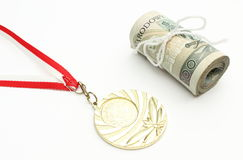 Gold medal and roll of tied banknotes on white background Royalty Free Stock Images