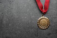 Gold medal with space for design on grey background, top view. Victory concept royalty free stock photography