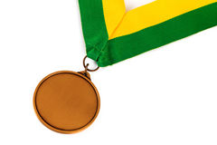 Gold medal on white background with blank face for text, Gold medal in the foreground. Royalty Free Stock Images