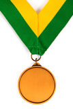 Gold medal on white background with blank face for text, Gold medal in the foreground. Royalty Free Stock Photos