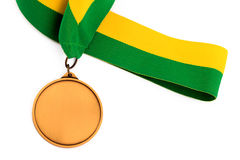 Gold medal on white background with blank face for text, Gold medal in the foreground. Royalty Free Stock Photo