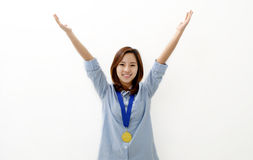 Gold Medal Winner. A young woman happily holds up her arms with a gold medal around her neck Royalty Free Stock Image