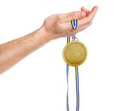 Gold medal winner in the hand. On a white background Royalty Free Stock Photos