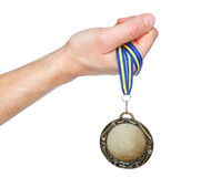 Gold Medal winner in the hand. On a white background Royalty Free Stock Photography
