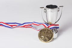 Gold medal winner and silver trophy. Gold medal winner on a ribbon entwined around a silver trophy to be awarded to the champion in a sporting event with copy Stock Photos