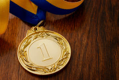 Gold medal on a wooden table. Gold medal in the foreground on yellow blue ribbon Royalty Free Stock Photos