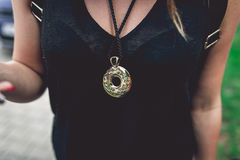 Gold medallion hanging on woman`s neck. royalty free stock photography
