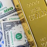 Gold metal ingot bullion on the background of dollar and euro bills royalty free stock images