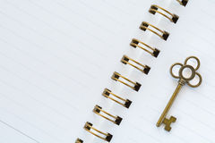 A gold metal key on white paper.  stock images