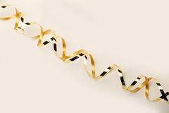 Gold metallic curly ribbon on a cream background Royalty Free Stock Photo