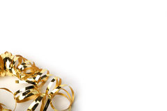 Gold metallic curly ribbon on a cream background Royalty Free Stock Image