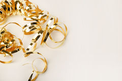 Gold metallic curly ribbon on a White background Royalty Free Stock Images