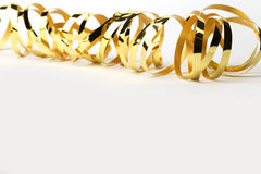 Gold metallic curly ribbon on a White background Royalty Free Stock Photo