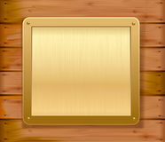 Gold metallic plate on a wooden wall. Vector Stock Photography