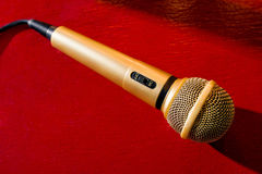 Gold microphone on dark background with many lights. Gold microphone on red wooden and dark background with many lights Stock Photo