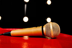 Gold microphone on dark background with many lights. Gold microphone on red wooden and dark background with many lights Royalty Free Stock Photos