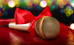 Gold microphone with red bow. On dark background Royalty Free Stock Photo