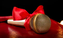 Gold microphone with red bow Royalty Free Stock Image