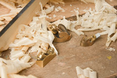Gold miniature wood planer on wooden plank Stock Images