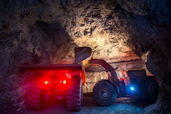 Gold mining underground. Loading truck with golden ore in the tunnel Royalty Free Stock Photos