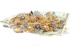 Gold and money. Gold jewelry laying on dollars, white background Stock Image