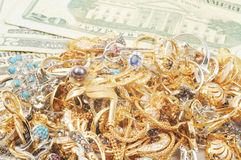 Gold and money. Stack of gold jewelry with dollars , close up Stock Photo