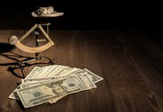 Gold and money. Gold nugget lying on the scales and dollar bills on the table stock photos