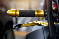 Gold motorcycle handle on street background Stock Photos