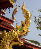 Gold naga statue. In Thai temple with blue sky Royalty Free Stock Photography