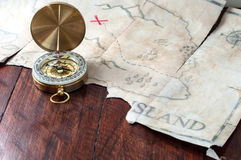 Gold nautical compass on old retro pirate map with red mark cross. Fake treasure map on wooden table Royalty Free Stock Image