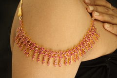 Gold necklace. Woman wearing gold and ruby necklace on shoulder Stock Photos