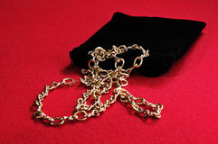 Gold necklace with black bag Royalty Free Stock Photography