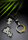 Gold necklace. With diamonds lies on the water with flowers and palm branch on a black background Stock Photos