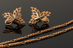 Gold necklace and earrings in the form of maple leaves embellish. Ed with platinum on black stock photography