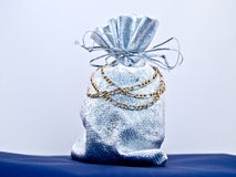 Gold necklace gift against bluish background Royalty Free Stock Images