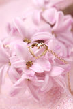 Gold necklace with heart on hyacinth. Gold necklace with heart on pink hyacinth. Shallow dof royalty free stock photo